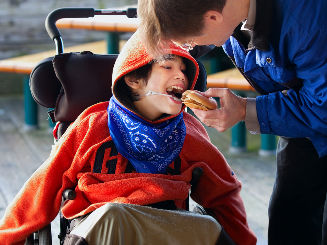 A person helping a child eat food